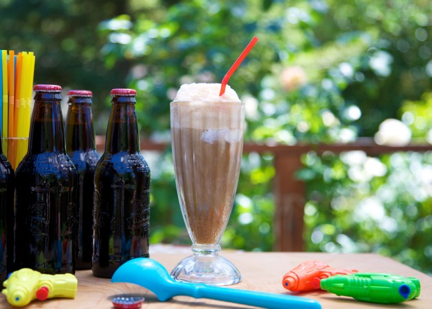 Root beer float outdoors with ice cream scoop, straws, squirt guns and bottles