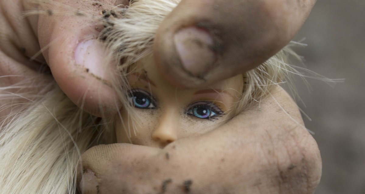 barbie doll head being gripped by dirty hands