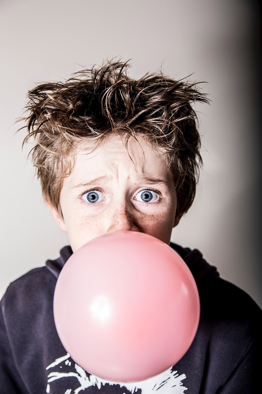 Young boy blowing bubble with chewing gum
