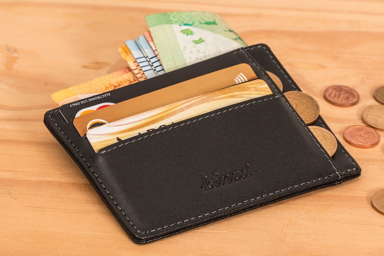 Wallet holding credit cards with coins coming out