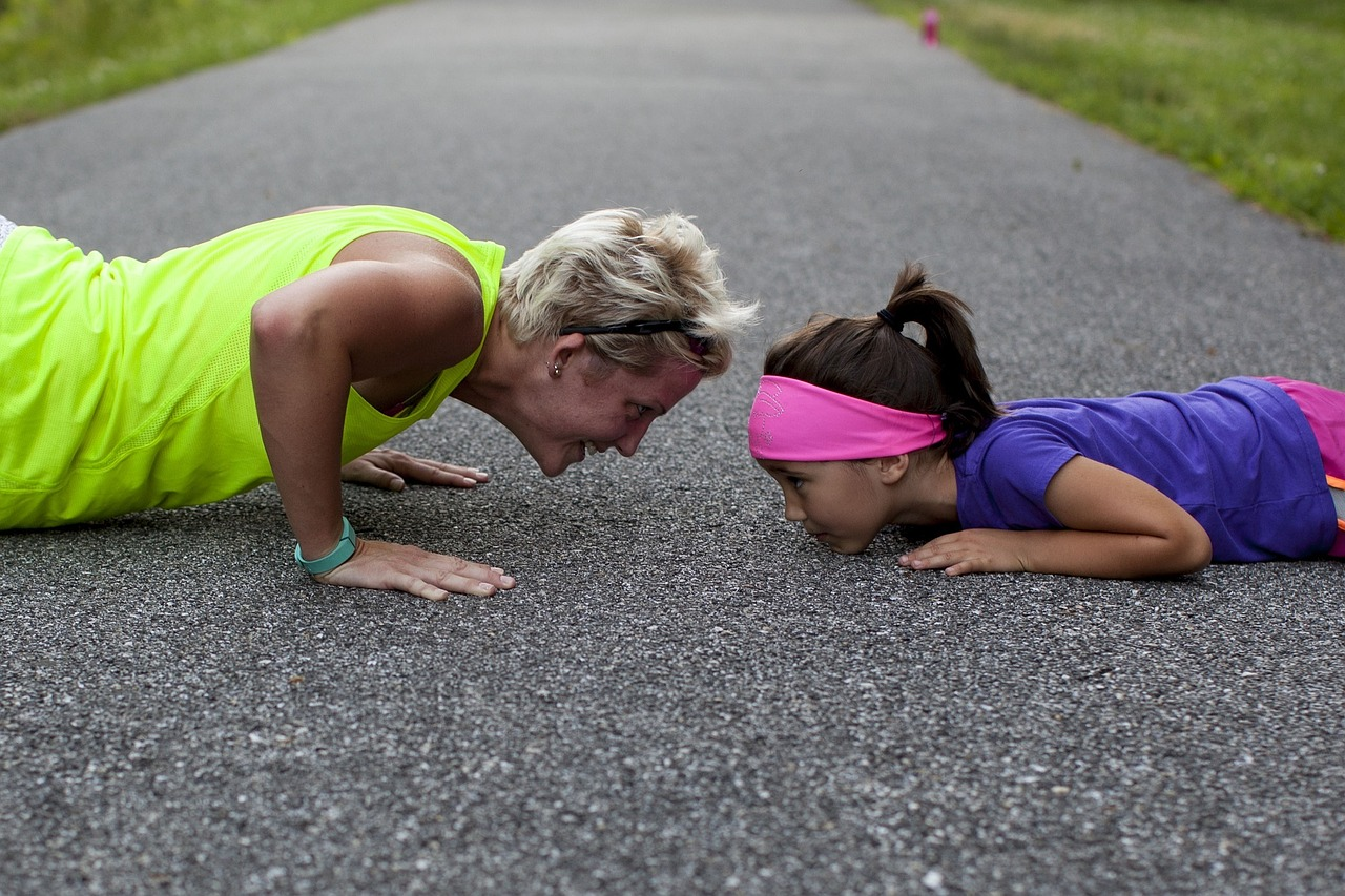 Mother and daughter doing pushups on concrete