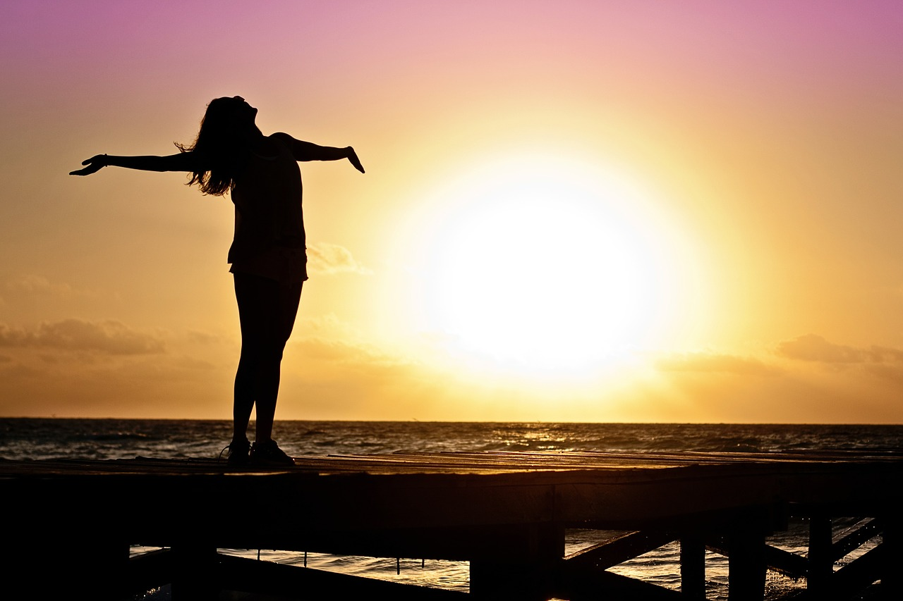 Woman looking up at the sky with arms open and sunset in background