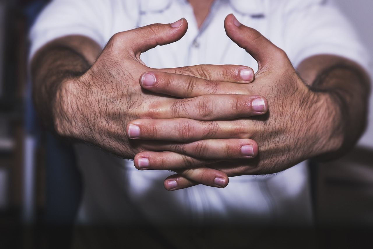Person's hands out and fingers laced