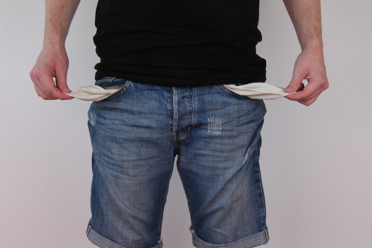 Man pulling out the inside of his pockets showing they are empty