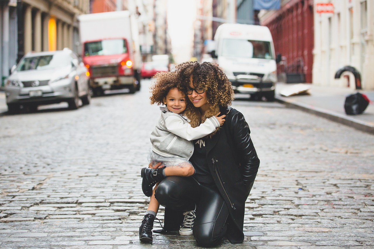 Single mother hugging daughter in the street