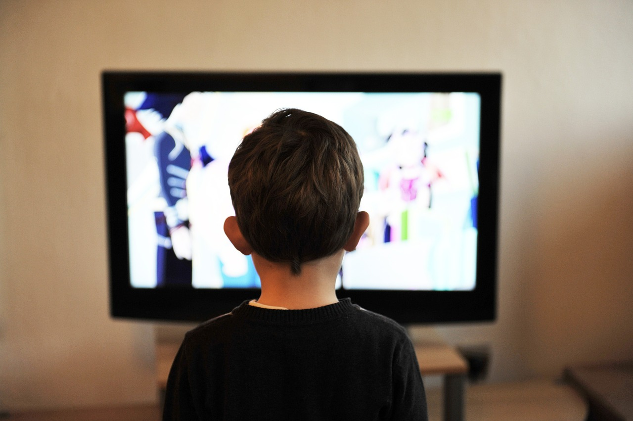 Young boy sitting in front of television screen
