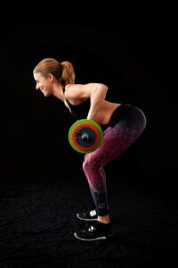 Woman bent over lifting dumbbells